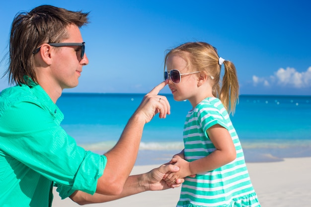 Father apply sunblock cream on his little child nose