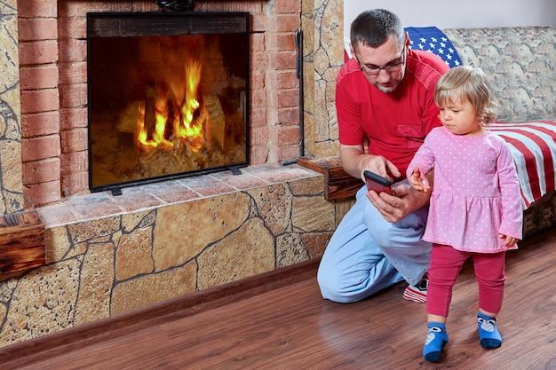 아버지는 딸에게 스마트 폰을 보여주고 있으며, 그들은 벽난로 근처에 서 있고 소녀는 장치에 관심이 있습니다.