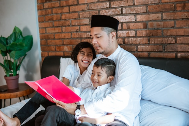 Father asian reading a book for his two children