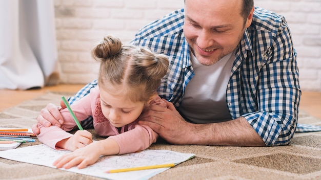 Father assisting girl in drawing while lying on carpet at home