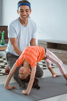 Father assisting his daughter to do stretching at home. kid exercising with parent doing gymnastic