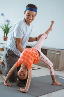 Отец помогает дочери делать растяжку дома. ребенок тренируется с родителями делает гимнастику
