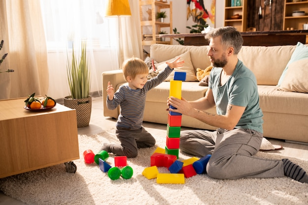 Father assisting son to build tower from cubes
