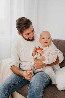 赤ちゃんを抱いて家にいる父