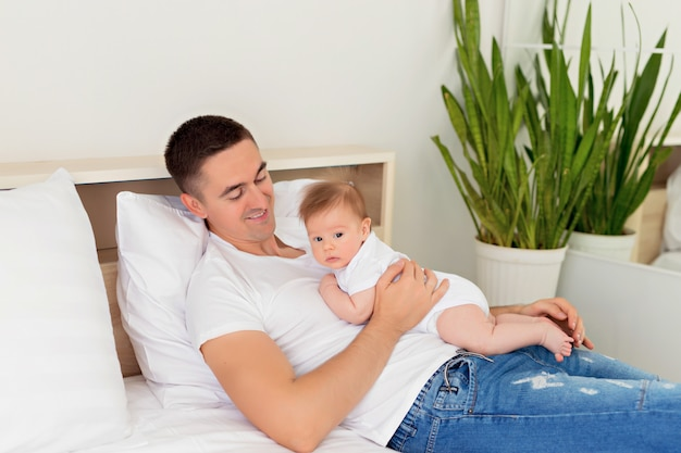 Father and baby son are playing on a white bed in a sunny bedroom.