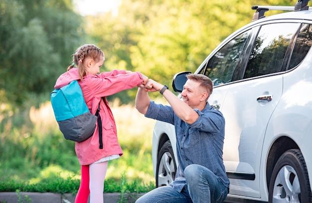 車の近くの屋外の学校に戻る娘と拳を叩いて父
