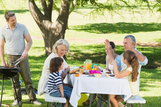 Father at barbecue grill with family having lunch in park