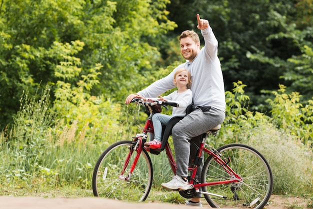 Father on bicycle pointing for daughter