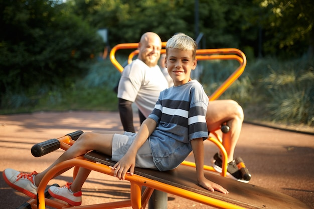 Father and boy doing abs exercise, sport training on playground outdoors. the family leads a healthy lifestyle, fitness workout in summer park