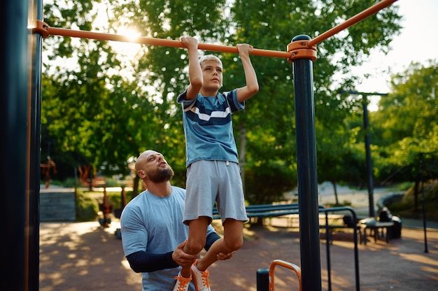Father and boy, exercise on horizontal bar