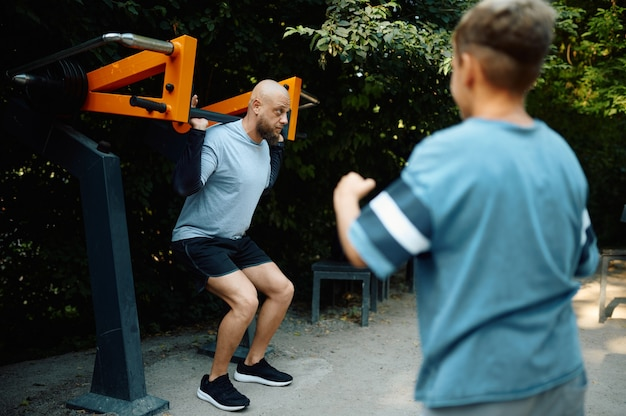 Father and boy on exercise machine, sport training