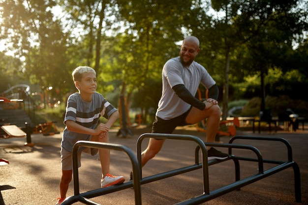 Father and boy, stretching exercise on playground