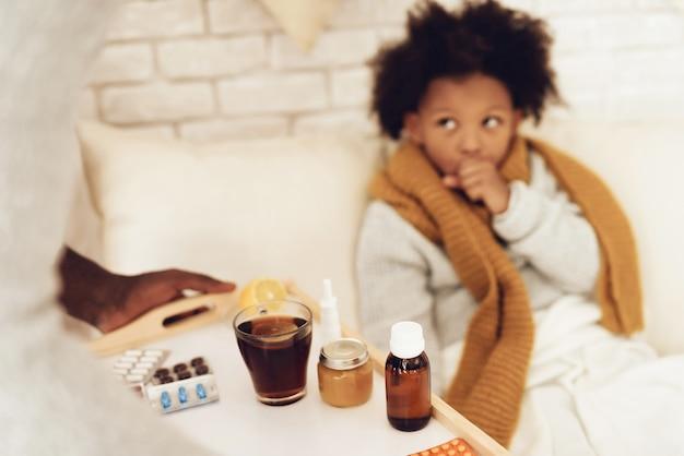 Отец приносит дочери лекарства от кашля и чай.