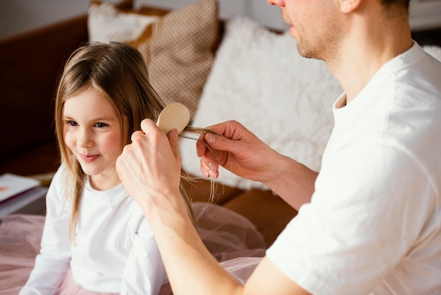Padre che spazzola i capelli di sua figlia