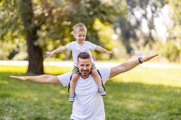 아버지는 그의 어깨에 그의 아들을 운반합니다. 육아와 행복한 어린 시절. 아버지와 아들은 화창한 여름날 자연 속에서 재미있는 시간을 보냅니다. 그 아버지에 그 아들 같은