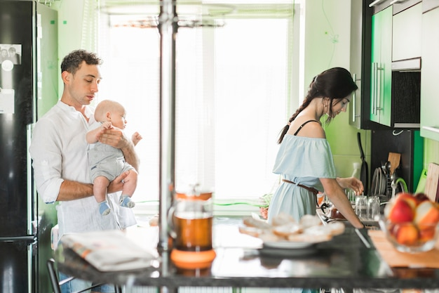 Father carrying baby with his wife working in the kitchen