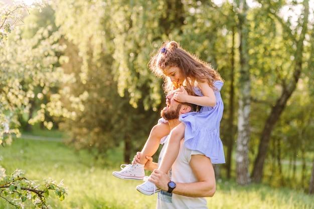 肩に娘を運んでいる父