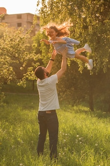 Father carrying his daughter up in the air