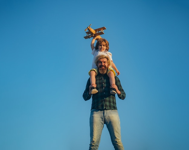 Father carrying his son on shoulders. father and son playing with toy plane outdoor. family holiday, parenthood. fathers day.