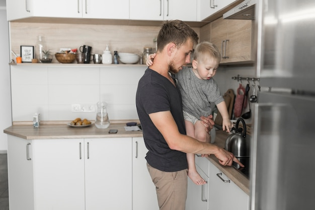 Father carrying his son showing something on kitchen counter