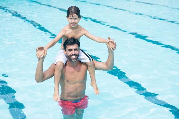 プールで肩に息子を運ぶ父