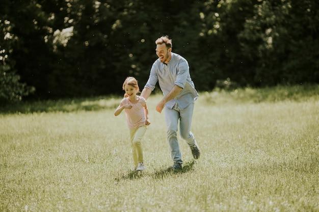 Отец преследует свою милую маленькую дочь, играя в парке