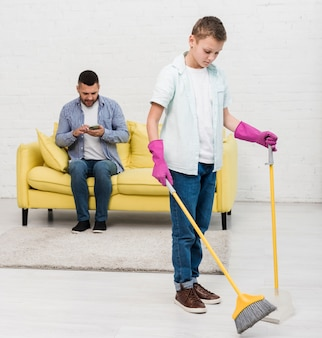 Father checking phone while son uses broom
