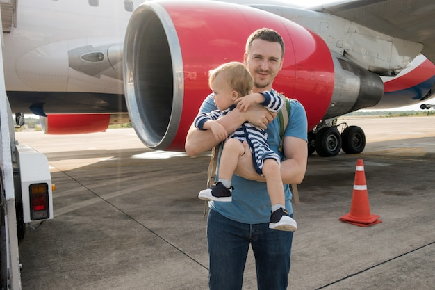 Father and child boarding on plane in airport