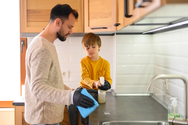 Father and child cleaning the kitchen