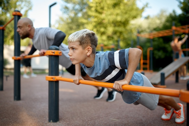 Father and child doing exercise, sport training on playground outdoors. the family leads a healthy lifestyle, fitness workout in summer park
