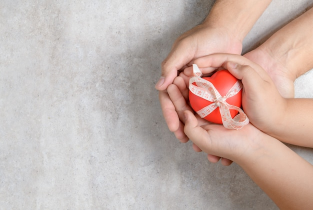 Father and child hands holding red heart
