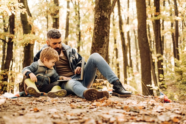 Father and child son in autumn park having fun and laughing