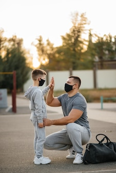 A father and child stand on a sports field in masks after training during sunset.
