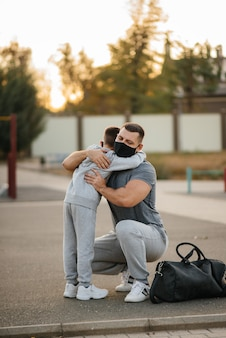 Father and child stand on sports field in masks after training during sunset