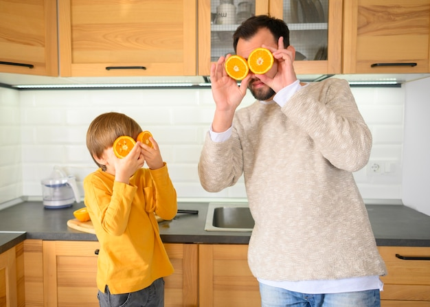 Father and child using halves of oranges to cover their eyes