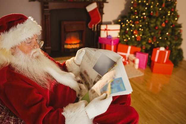Father christmas reading newspaper on the couch