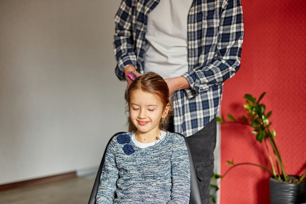 Отец расчесывает, расчесывает волосы дочери дома, отец и дочь улыбаются, семейные моменты, проводят время вместе.