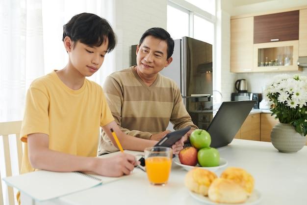 自宅の台所のテーブルで勉強または宿題をしている彼の10代の息子を制御する父