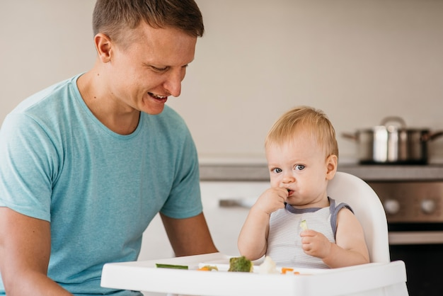 Father and cute baby in highchair eating