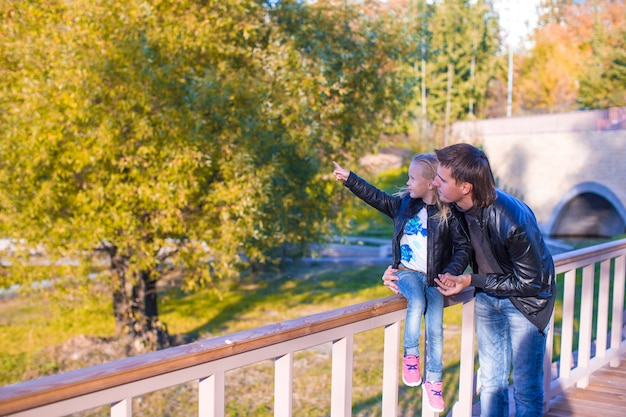 Father and cute daughter in autumn park outdoors