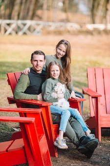 Father and cute daughters with dog outdoors