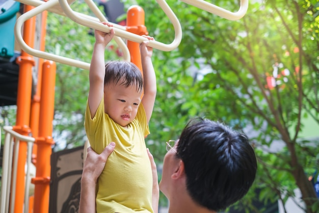 Father and cute little asian 2 - 3 years old toddler baby boy child having fun exercising outdoor and dad help catch up on monkey bars equipment at playground