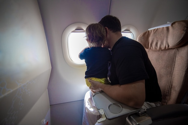 Father and cute toddler sit on an airplane and look at sky through the porthole first flight