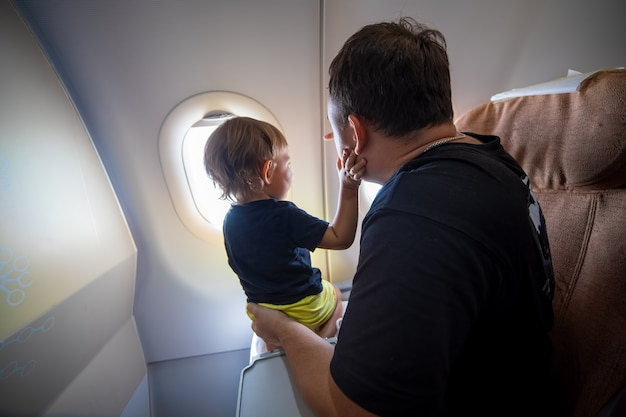 Father and cute toddler sitting on an airplane and looking at the sky through the porthole. first flight concept, traveling with children