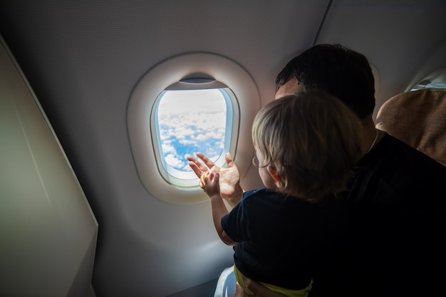 Father and cute toddler sitting on an airplane and looking at the sky through the porthole first