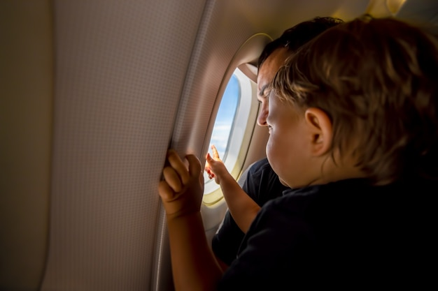 Father and cute toddler sky at porthole. first flight concept, traveling with children.