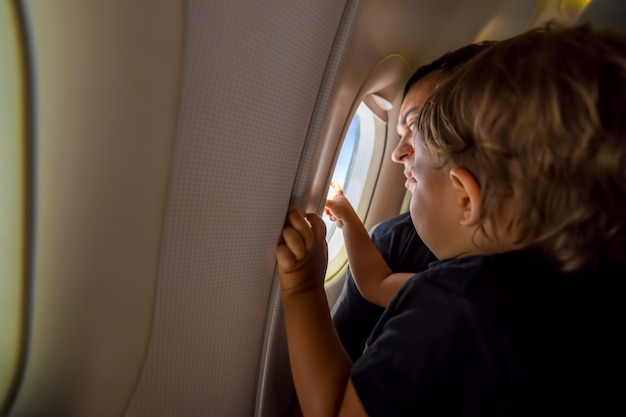 Father and cute toddler sky at porthole first flight concept traveling with children