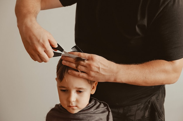 A father cuts his son's hair with scissors at home