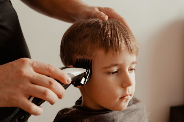 A father cuts his son's hair with a trimmer at home