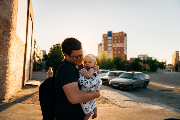 Father dad holding newborn baby girl infant on hands outdoors summer sunset evening